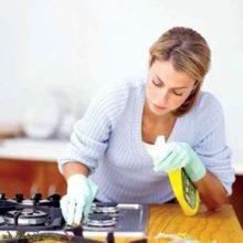 Женщина очищает газовую плиту