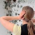 Женщина смотрит на плесень на стенах