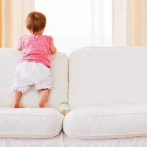Ребенок стоит на диване