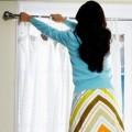 Женщина снимает тюль