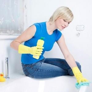 Женщина очищает налет в ванной